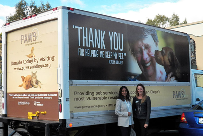 (l to r) Geraldine D'Silva, executive director of PAWS San Diego with Kelli Schry, public relations manager for the San Diego Humane Society, in front of one of PAWS San Diego's home-delivery trucks (Photo by B.J. Coleman)