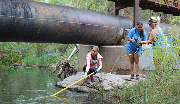 (l to r) Bryanna Paulson, Dana Tomasevic and Vicki Conlon test the electrical conductivity of the river near Old Mission Dam. (Photo by Jeremy Ogul)