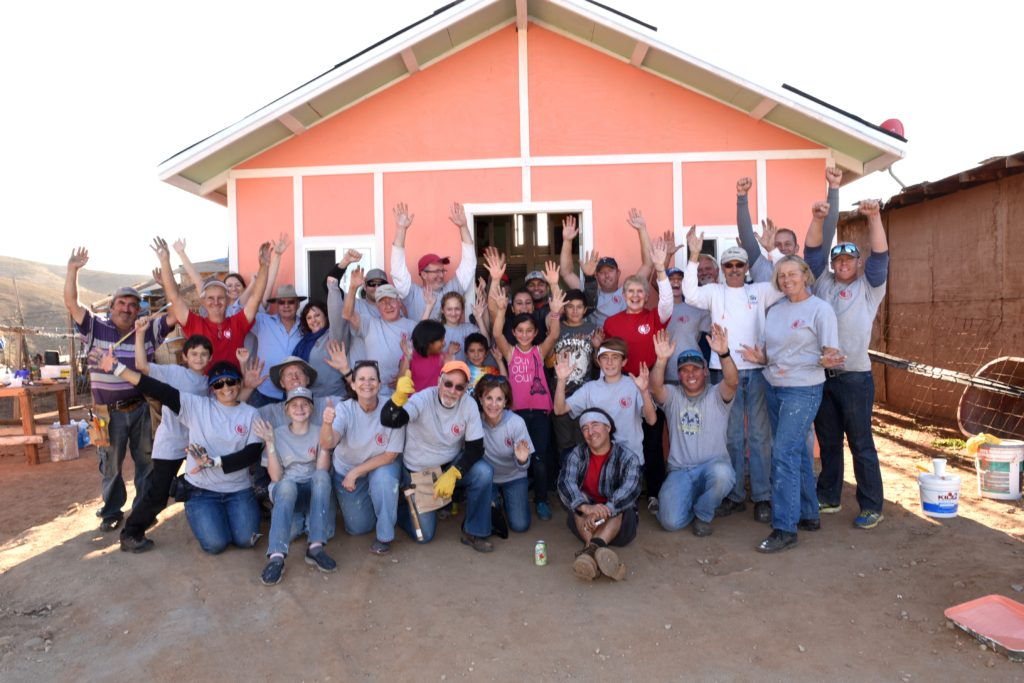 IRT volunteers celebrate after building a home for an impoverished family in Tijuana. Volunteers build homes in this community in just one day for impoverished families with children.